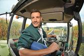 Agricultor manejando el tractor en un campo de maíz — Foto de Stock