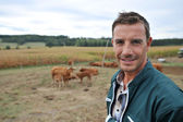 Herdsman standing in front of cattle in country field — Stock Photo