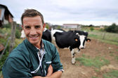 Smiling cow breeder standing in in front of cow herd — Stock Photo