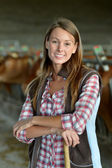 Smiling farmer woman standing in barn — Stock Photo