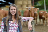 Femme d'agriculteur souriante permanent par le bétail à l'extérieur — Photo