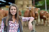 微笑的站在外面的牛的农夫女士 — 图库照片