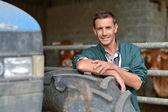 Beau fermier penche dans la grange sur la roue du tracteur — Photo