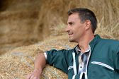 Portrait of smiling farmer standing by haystacks — Stock Photo