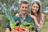 Portrait of couple of farmers holding basket of vegetables — Stock Photo