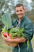 Portrait of smiling farmer holding vegetables basket — Stock Photo