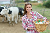 Smiling young farmer carrying bottles of fresh milk — Foto Stock