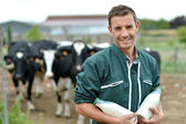 Farmer standing in front of cow herd with bottles of milk — Stock Photo