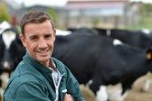 Berger debout devant les bovins en ferme — Photo