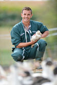 Cheerful farmer holding duck in his arms — Stock Photo