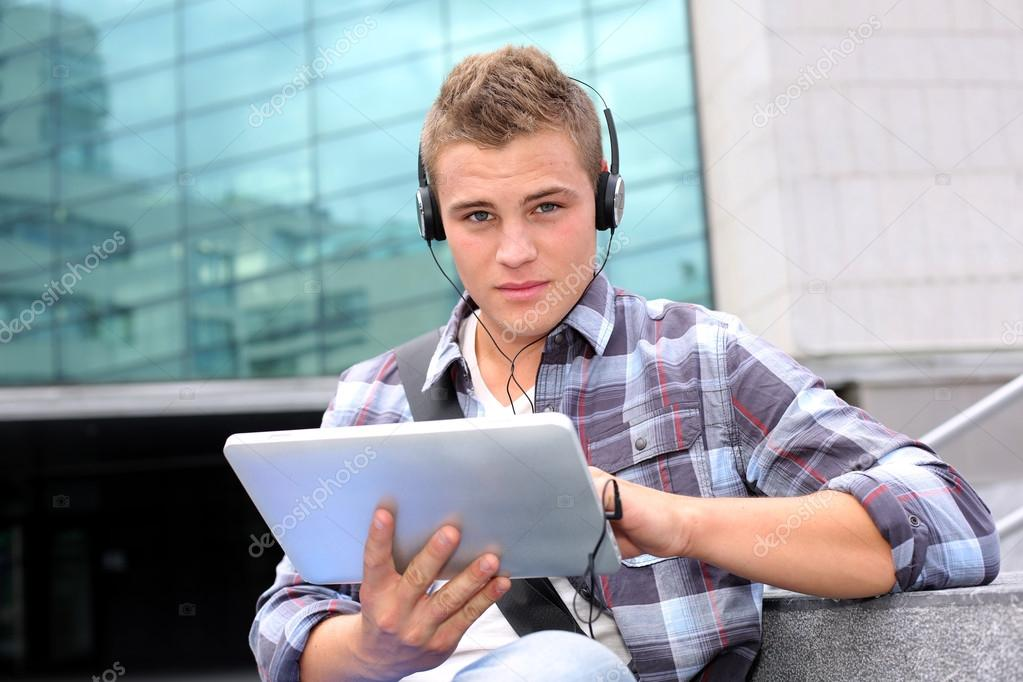 College student using digital tablet and headphones — Stock Photo #13964440