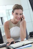 Businesswoman at her desk booking meeting hours on agenda — Stock Photo