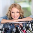 Portrait of blond woman leaning on clothes hanger — Stock Photo