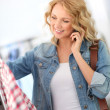 Woman in store talking with girlfriend on the phone — Stock Photo