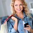 Woman using mobile phone while shopping — Stock Photo