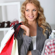 Cheerful woman holding shopping bags — Stock Photo