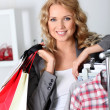Cheerful woman holding shopping bags — Stock Photo #18197045