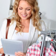 Beautiful woman in garment store using electronic tablet — Stock Photo #18197119