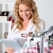 Beautiful woman in garment store using electronic tablet — Stock Photo