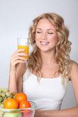 Beautiful blond woman drinking fruit juice — Stock Photo
