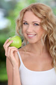 Portrait of beautiful woman eating green apple — Stock Photo