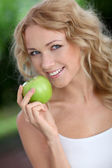Portrait of beautiful woman eating green apple — Stock Photo