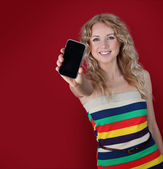 Beautiful woman holding mobilephone towards camera — Stock Photo