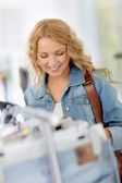 Beautiful blond woman looking at price tags in store — Stock Photo