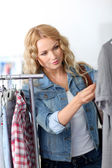 Attractive woman in clothing store checking price — Stock Photo