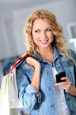 Woman using mobile phone while shopping — Stock fotografie