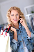 Woman using mobile phone while shopping — Stok fotoğraf