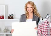 Mujer hermosa en la tienda de ropa con tablero de mensajes — Foto de Stock