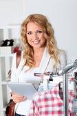 Mujer hermosa en la tienda de ropa usando tableta electrónica — Foto de Stock