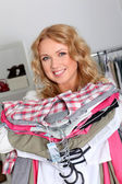 Mujer en tienda de ropa con pila de ropa — Foto de Stock