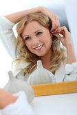 Portrait of beautiful woman in store trying earings — Stock Photo
