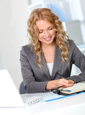 Businesswoman in office writing on agenda — Stockfoto