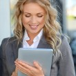 Businesswoman standing outside with electronic tablet — Lizenzfreies Foto