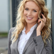 Saleswoman using mobile phone and digital tablet — Stock Photo