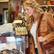 Woman looking at chocolate and treats by shopwindow - Stock Photo