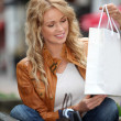 Trendy beautiful woman in town with shopping bags — Stock Photo