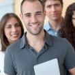 Portrait of student standing with workgroup — Stock Photo #18207045