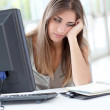 Exhausted young woman sitting in front of computer — Stock Photo