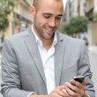 Relaxed businessman with mobile phone in town  — Stock Photo