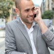 Relaxed businessman with mobile phone in town — Photo
