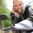 Young man sitting in motorcycle with telephone — Stock Photo