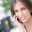 Smiling beautiful girl talking on telephone in town — Stock Photo