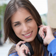 Beautiful teenager sitting outside with headphones — Stock Photo