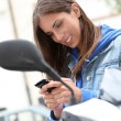 Young woman sitting on motorbike outside — Stockfoto