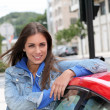 Young woman standing by red car  — Stock Photo
