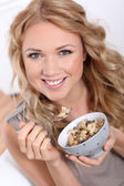 Portrait of beautiful woman eating cereals — Stock Photo